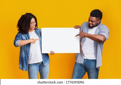 Cheerful black couple holding and pointing at blank advertising board with copy space for text, standing on yellow background