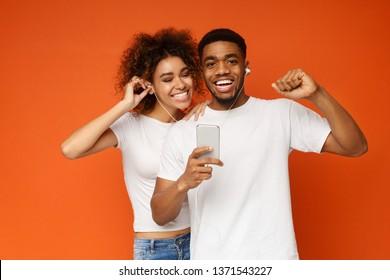 Cheerful black couple sharing headphones, enjoying favorite music on smartphone, orange background