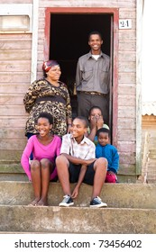 Cheerful black family on the steps infront of their rural house.