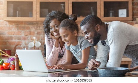 Cheerful black family using laptop at kitchen, looking for healthy food recipe, panorama with copy space