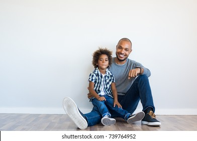 Cheerful black father sitting on floor with smiling son and leaning on blank wall with copy space. Young african boy sitting on father lap in a new home. Happy father and child looking at camera.