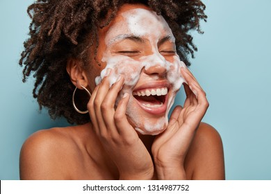Vrolijk zwart vrouwelijk model past schuimende reiniger toe, heeft een schone frisse gezonde huid, lacht breed, Afro bossige kapsel, staat blote schouder tegen blauwe achtergrond. Schoonheid en vrouwelijk concept