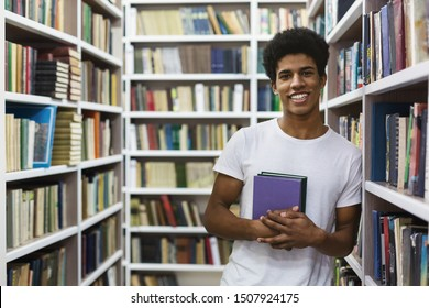 Cheerful black guy staying between bookshelves at library, holding book, empty space