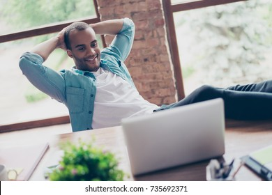 Cheerful black guy is watching at his laptop screen, at his work place, with arms behind the head, resting, smiling, in the office