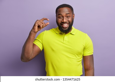 Cheerful black man with bright smile, shows white teeth, shapes something very tiny with hand, wears yellow t shirt, stands over purple background, pretends holding small object, isolated on lilac