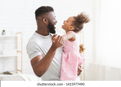 Cheerful black man dancing with his little daughter, having fun and laughing together at home, free space