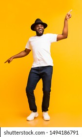 Cheerful black man in hat dancing and pointing index fingers aside on yellow studio background