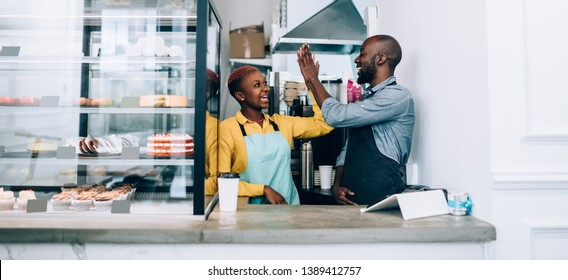 Cheerful black man and woman in aprons giving high five to each other while celebrating success and standing behind counter in small restaurant