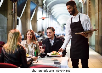 Cheerful black waiter serving terrace restaurant guests at table.Focus on the man