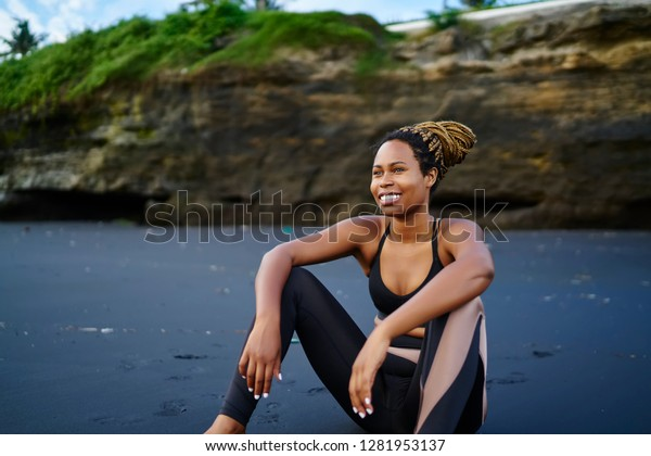 Cheerful black woman dressed in stylish sportswear looking away during break from energetic and active workout outdoors, happy smiling female athletic resting on beach on morning time for sport