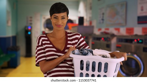 Cheerful black woman with laundry basket poses for portrait