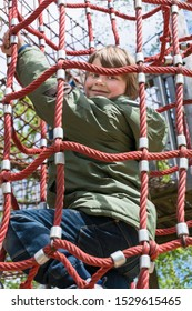 Cheerful blond boy climbing on cables at playground