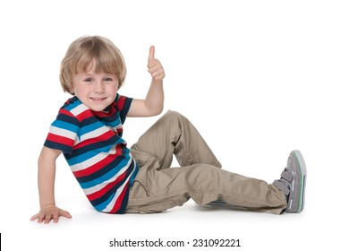 A cheerful blond boy sits on the floor and holds his thumb up against the white background