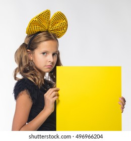 cheerful blond girl in a black dress with a yellow sheet of paper for notes on a white background
