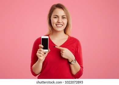Cheerful blonde female with broad smile indicates at blank screen of smart phone for your advertising content, dressed in red sweater, isolated on pink background. Technology and people concept