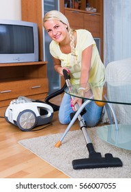 Cheerful  blonde girl hoovering in living room and smiling