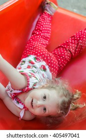 Cheerful blonde girl lying on red plastic playground slide and looking at camera