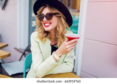 Cheerful  blonde short-haired  stylish girl resting in street cafe , drinking tasty pink cocktail, enjoying summer weekends. Wearing  trendy hat and sunglasses.  Bright make up.