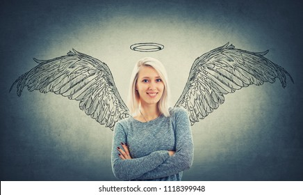 Cheerful blonde woman with blue eyes and crossed hands imagining herself as an angel with wings behind her back and a halo above head. Super power idea, self development, success and freedom concept.