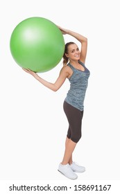 Cheerful blonde woman holding a fitness ball smiling at camera