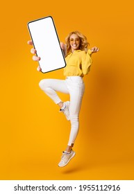 Cheerful blonde woman jumping up and showing newest smartphone with empty screen, enjoying new application for mobile device. Orange studio background, creative collage with mockup - Shutterstock ID 1955112916