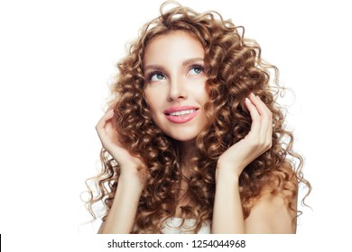Cheerful blonde woman touching her hair her hand and looking up. Haircare concept