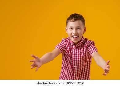 cheerful boy about 8 years old in a red checkered shirt stretched his arms out in front and smiled happily on yellow background. Close-up. the boy rejoices in success and victory. Discounts and sales