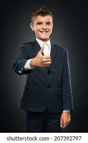cheerful boy in black suit showing thumbs up