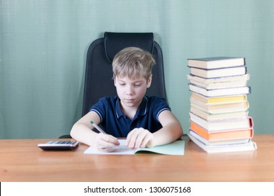 Cheerful boy with bunch of books is working on his homework at the table