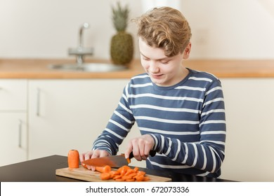 Cheerful boy chopping large orange carrots on wooden cutting board in kitchen with copy space