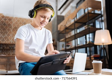 Cheerful boy creating music playlist on tablet