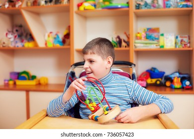 cheerful boy with disability at rehabilitation center for kids with special needs, solving logical puzzle