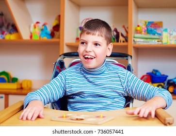 garçon joyeux avec handicap au centre de rééducation pour enfants ayant des besoins spéciaux, résoudre un casse-tête logique
