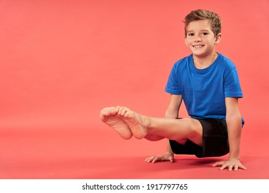 Cheerful boy doing exercise against red background