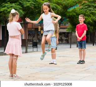 cheerful boy and girls in elementary school age jumping over chinese jumping rope at playground