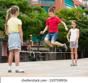 cheerful boy and girls in elementary school age playing with chinese jumping rope. Selective focus on girl