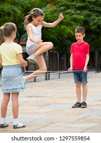 cheerful boy and girls in elementary school age playing with chinese jumping rope at playground
