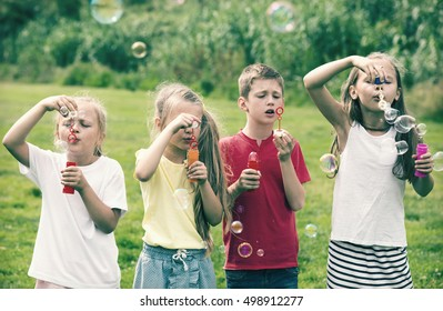 cheerful boy and girls in elementary school age standing on green grass and blowing bubbles