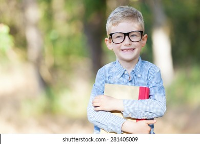 cheerful boy in glasses holding book and ready for school