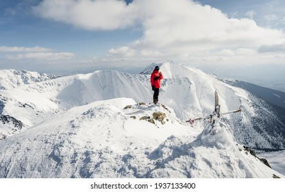 Cheerful boy is grimacing on top of the mountain where he climbed. View of the active man ski touring at mountains background at sunny winter day. Concepts: adventure, achievement, courage