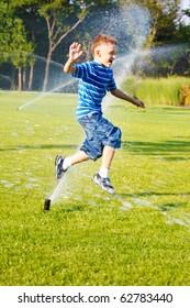 Cheerful boy having fun running from sprinkles