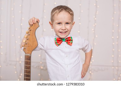 Cheerful boy in his room with his favorite guitar