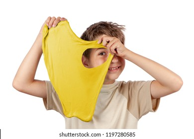 Cheerful boy holding a yellow slime and looking through its hole. Studio isolated on white background.
