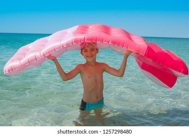 Cheerful boy holds a bright air mattress above his head, standing in the sea on a summer sunny day.