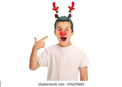 Cheerful boy posing with red reindeer ears and a red nose and pointing at them isolated on white background