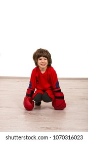Cheerful boy in red clothes sitting on boxing gloves and looking away