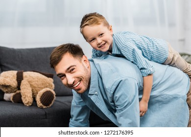 cheerful boy sitting on back of father standing on all fours and looking at camera in apartment