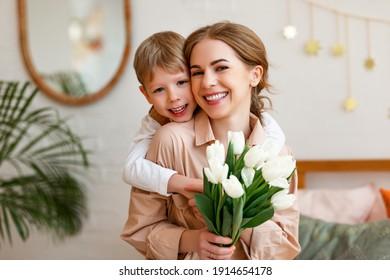 Fröhlicher Junge lächelt nach Kamera und umarmt Frau mit Strauß weißer Tulpen während der Feiertage Mütter Tag zu Hause