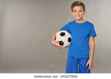 Cheerful boy with soccer ball standing against gray background