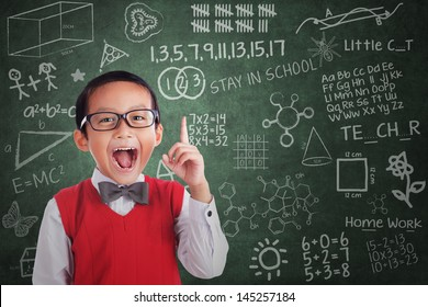 Cheerful boy student has idea in classroom